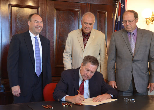 As Gov. John Kasich signs Sub. S.B. 150, the bill's sponsors and ODA director look on. L-R standing: Sen. Bob Peterson, Sen. Cliff Hite, ODA Director David Daniels. Photo: Ron Sylvester, OFU.