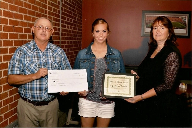 Darke County Farmers Union President, Todd Rhoades, presents a scholarship check to Second Place Winner of the Roger W. Paff Scholarship Essay Contest, Catey Fischer.  Melissa Sullenbarger, daughter of Roger Paff, presents a certificate at JT's Brew and Grill in Greenville, Ohio, during the Pre-Fair meeting.