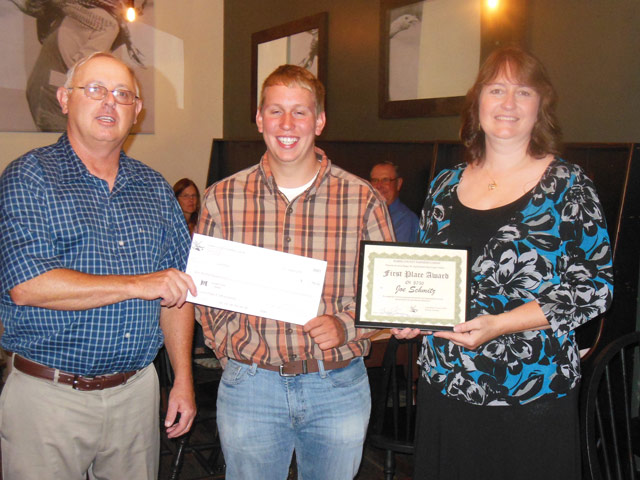 Darke County Farmers Union President, Todd Rhoades, presents a scholarship check to First Place Winner of the Roger W. Paff Scholarship Essay Contest, Joe Schmitz.  Melissa Sullenbarger, daughter of Roger Paff, presents a certificate at The Old Arcana in Arcanum, Ohio.