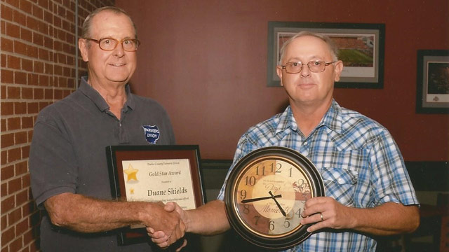 Duane Shields, left, past-president of the Darke County Farmers Union receives a reward from Todd Rhoades, president, Darke County Farmers Union.